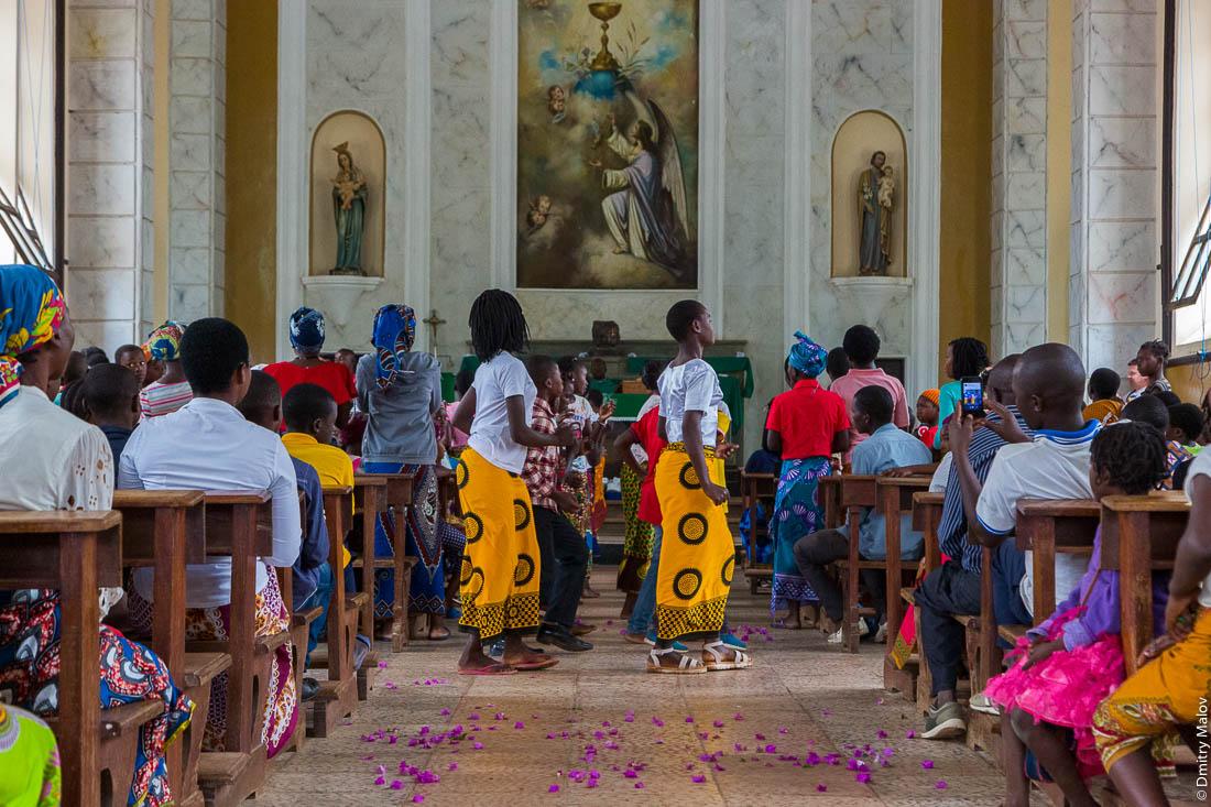 Воскресная месса. Чёрные девушки в жёлтых юбках танцуют в католическом храме, Santuário de S. M. Mãe do Redentor, Meconta, Mozambique.