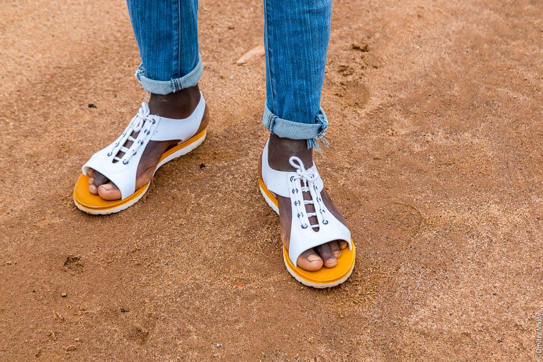 Ноги негра в бело-жёлтых сандалиях. Африка.