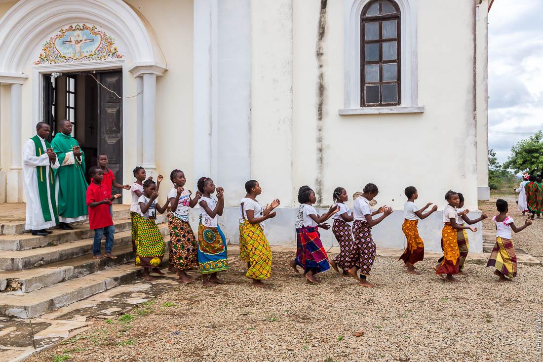 Воскресная месса, крёстный ход, процессия вокруг храма. Чёрные девочки в цветных юбках, священник в зеленых облачениях, Santuário de S. M. Mãe do Redentor, Meconta, Mozambique.