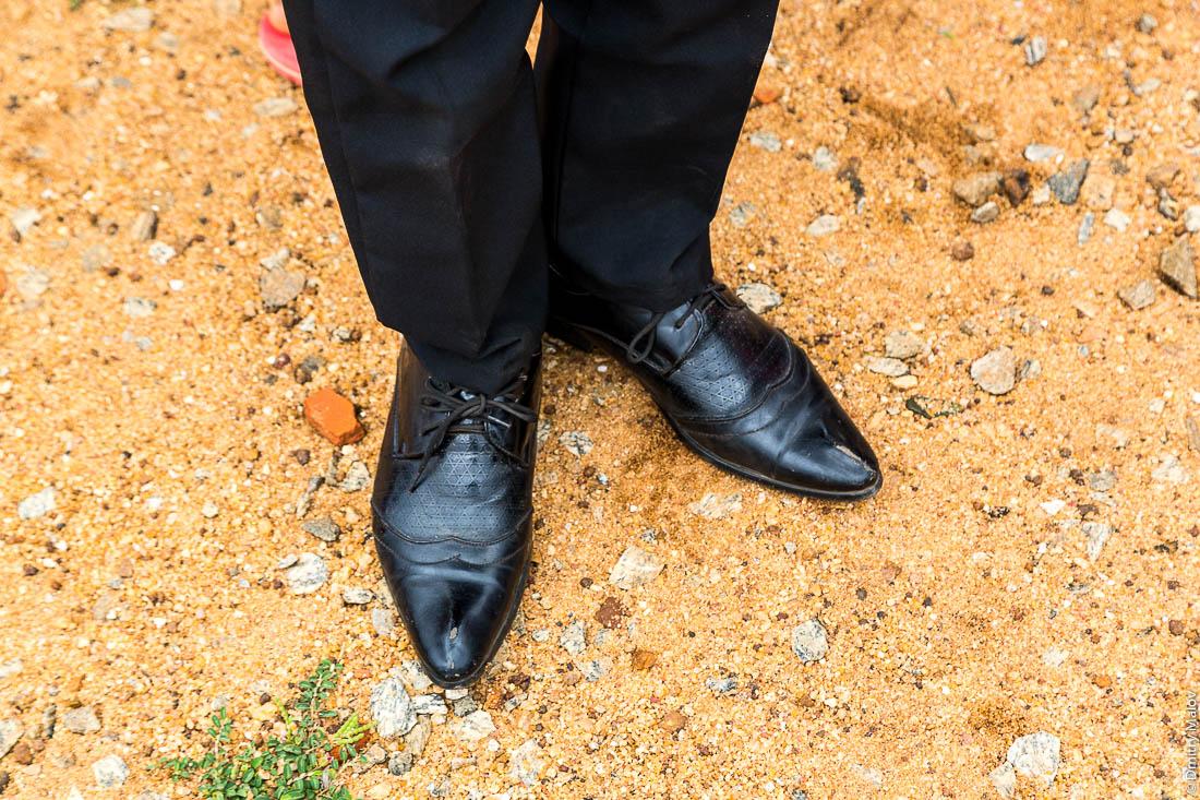 Мужские ноги в в чёрных брюках и черные мужские ботинки, глина, желтый песок, Африка