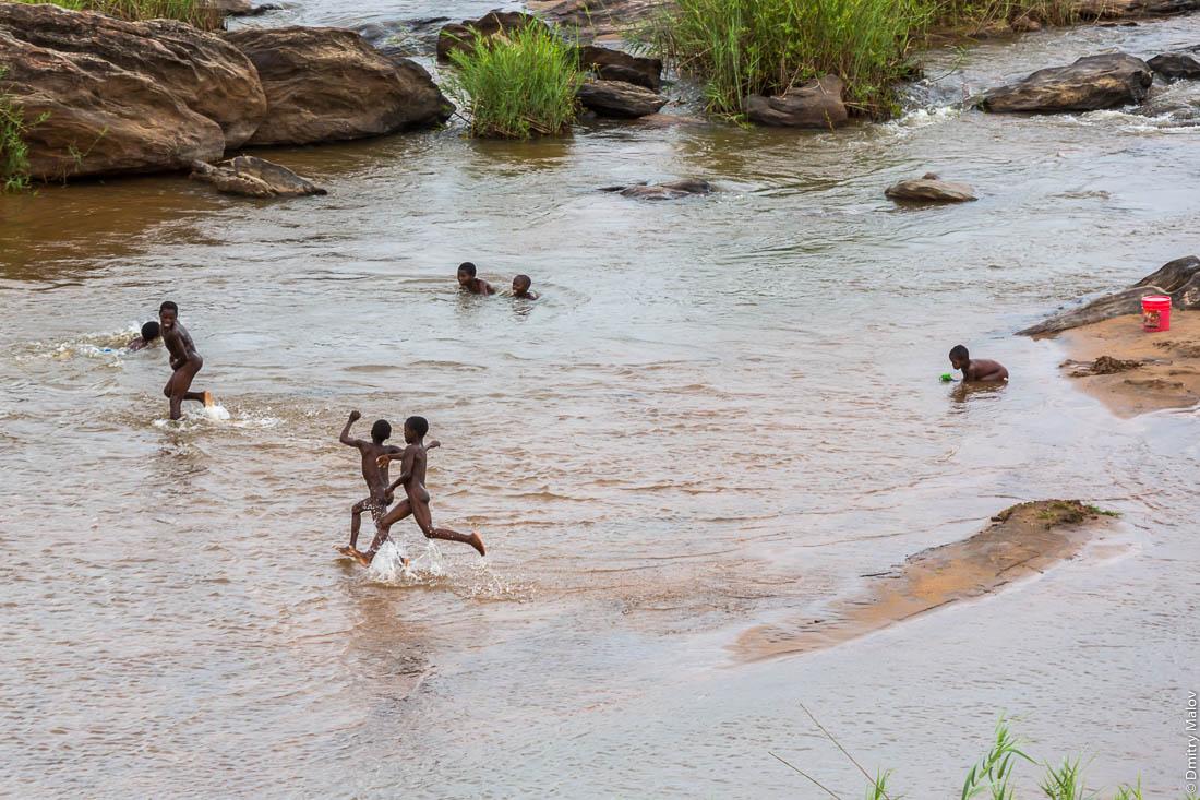 Чёрные мальчики бегают, резвятся в реке. Шоссе Нампула - остров Мозамбик, Мозамбик, Африка
