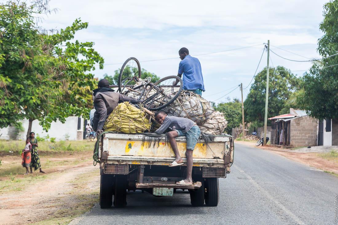 Африканцы, чёрные мужчины едут в кузове грузовика. Дорога Нампула - остров Мозамбик, Мозамбик, Африка