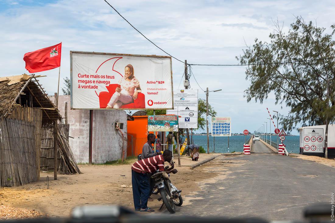 Въезд на мост на остров Мозамбик. Красные флаги. Шоссе Нампула - остров Мозамбик, Мозамбик, Африка