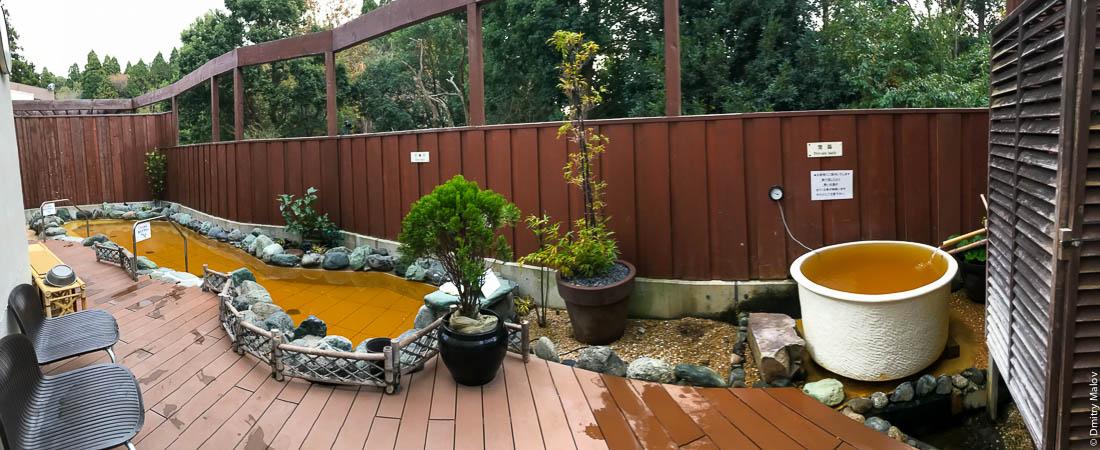 Двор с глиняным чаном и бассейном c горячей геотермальной водой в банном дворе под открытым небом в гостинице, онсен (сенто), Япония