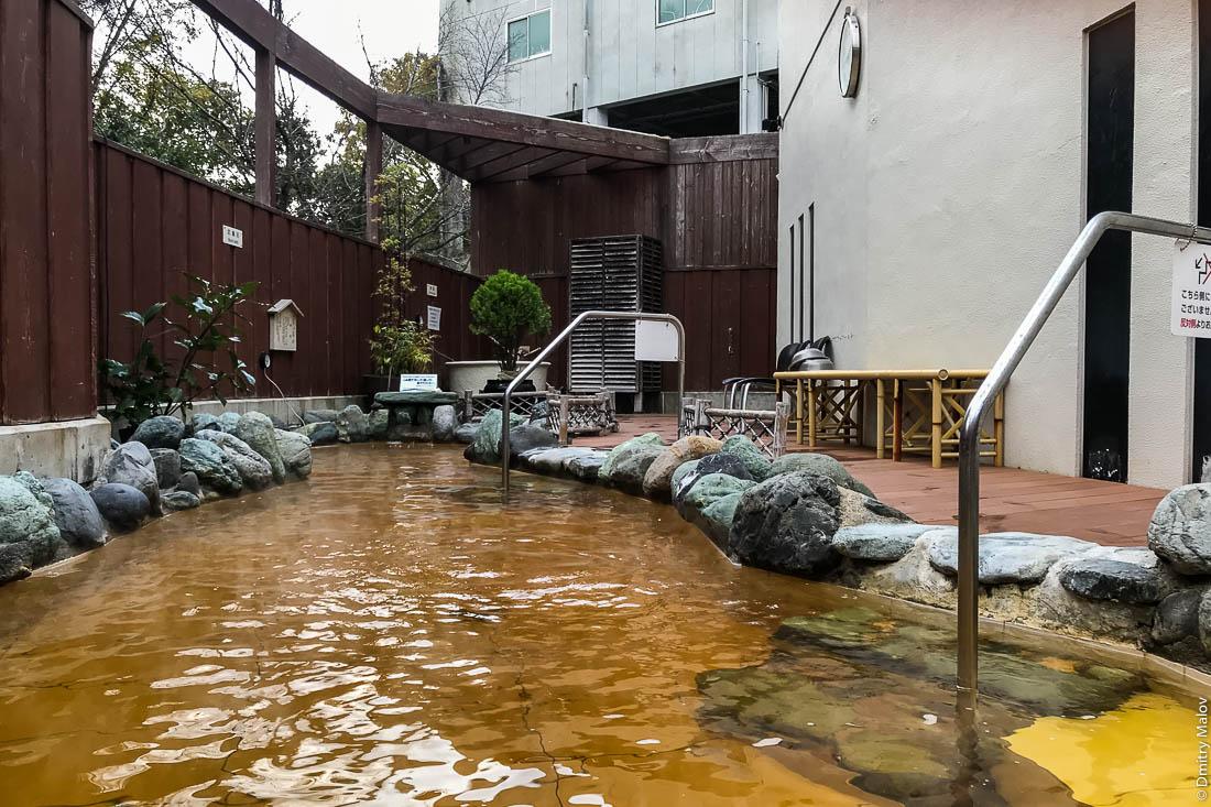 Бассейн под открытым небом с жёлтой горячей геотермальной водой в онсене (сенто) в гостинице, Япония