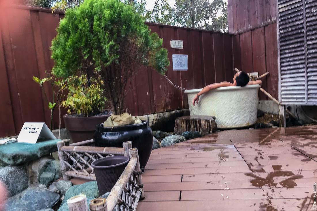 Мужчина парится/отмокает в глиняном чане c горячей геотермальной водой в банном дворе под открытым небом в гостинице, онсен (сенто), Япония